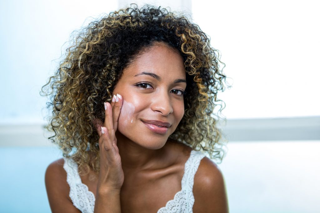 An African-American woman puts on moisturizer