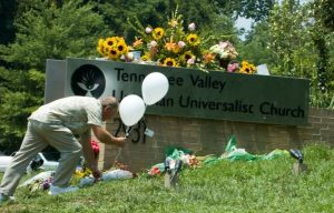A man leaves flowers at the Unitarian church in Knoxville, Tennessee, after a mass shooting