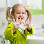 Little girl washing hands and showing soapy palms