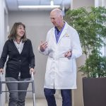 An orthopedic surgeon walks down the hall with a patient on a walker