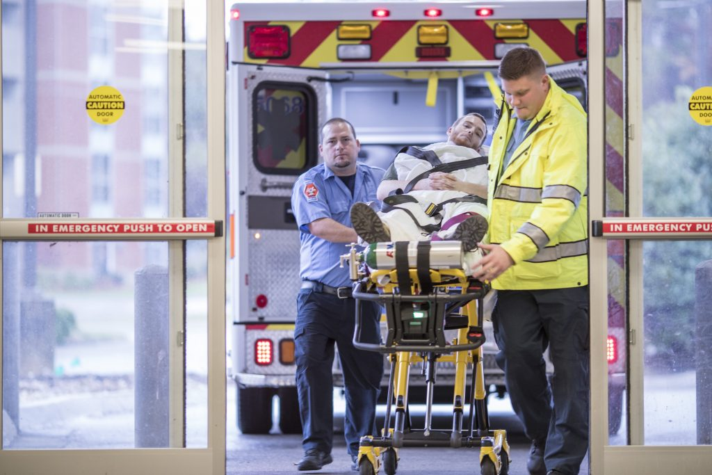 Trauma services providers wheel a patient on a stretcher into an emergency room