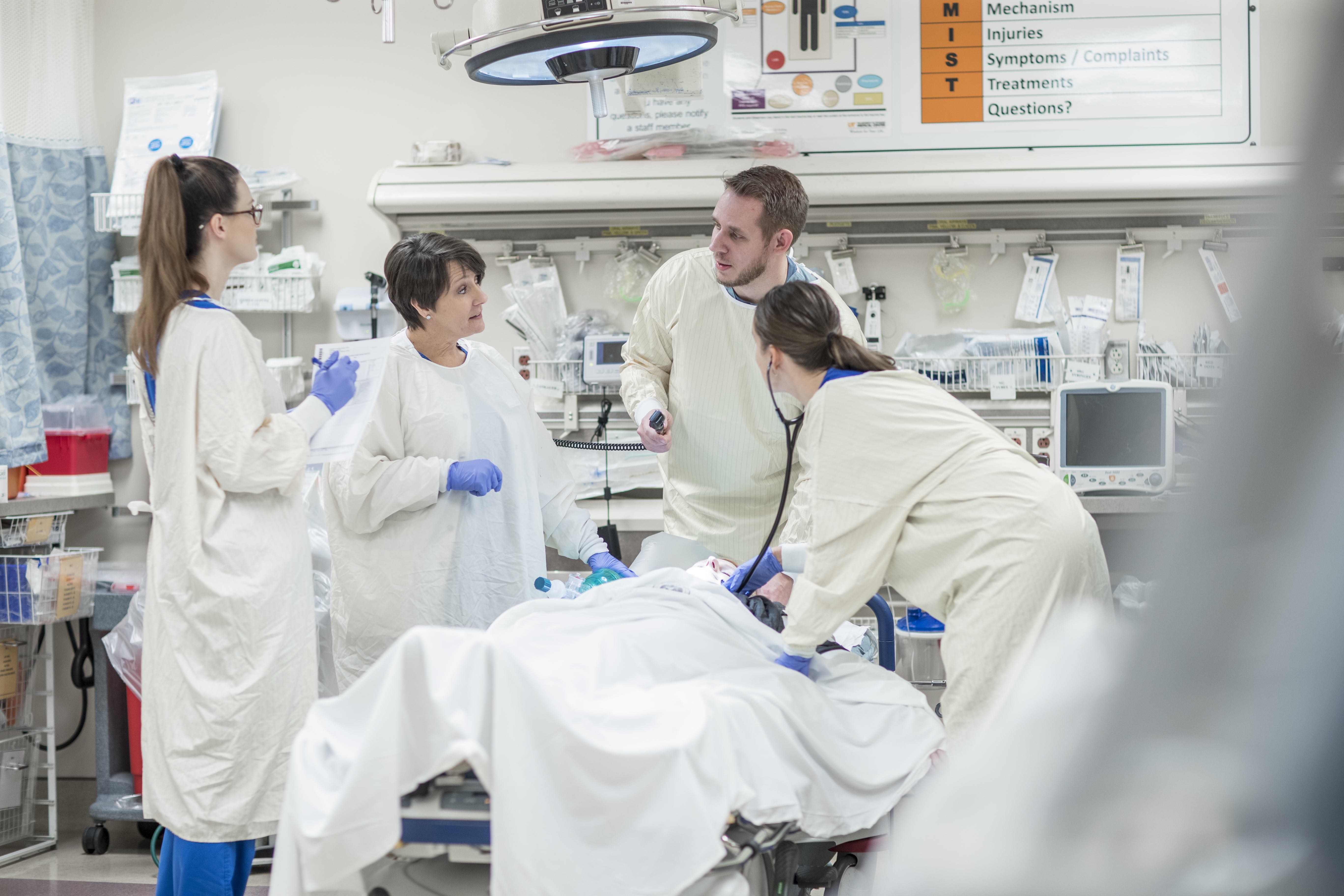 Emergency department physicians and providers work on a patient in an emergency room