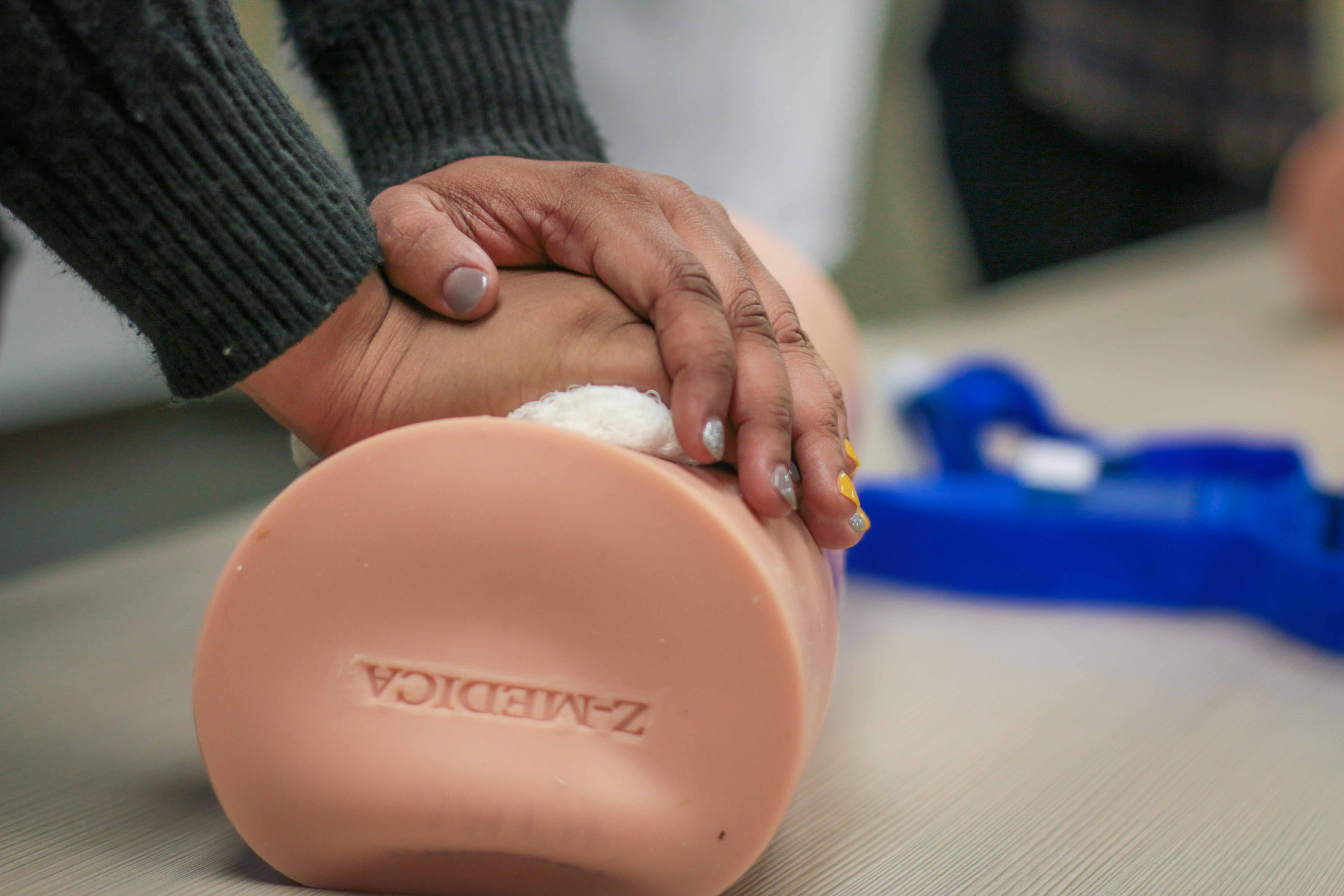 A woman practices life-saving techniques during a Stop the Bleed class