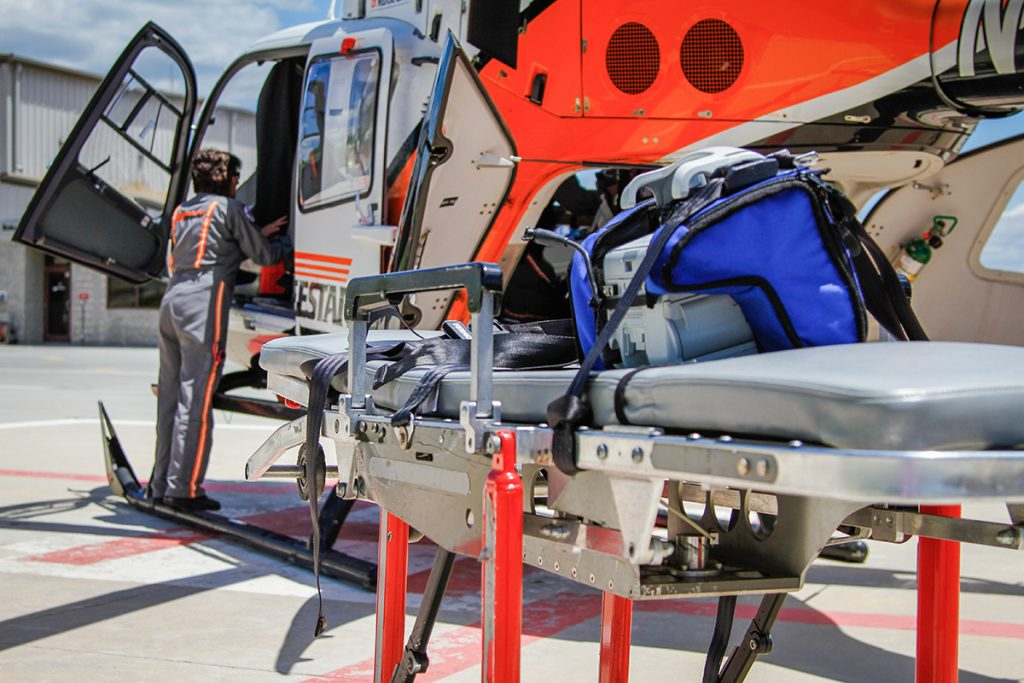 UT LIFESTAR aeromedical helicopter and stretcher on hospital landing pad