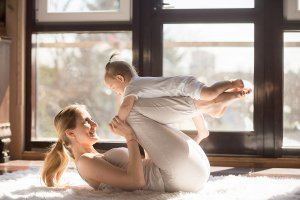 A young mom does yoga in the living room with her baby