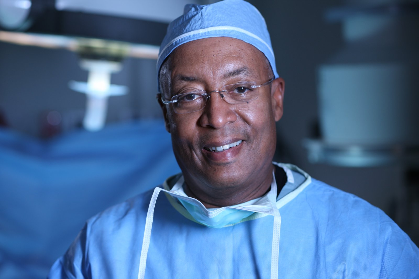 W. Bedford Waters MD poses in blue scrubs in an operating room