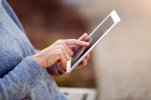 A closeup of a woman's hands as she sits on a park bench holding an iPad tablet