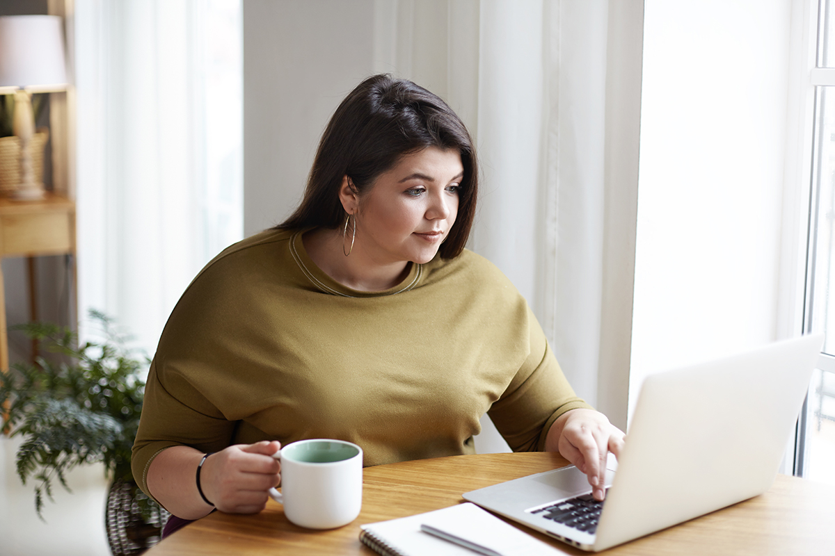 A Latina woman uses her laptop at the kitchen table