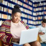 A Black woman works on her laptop in a library