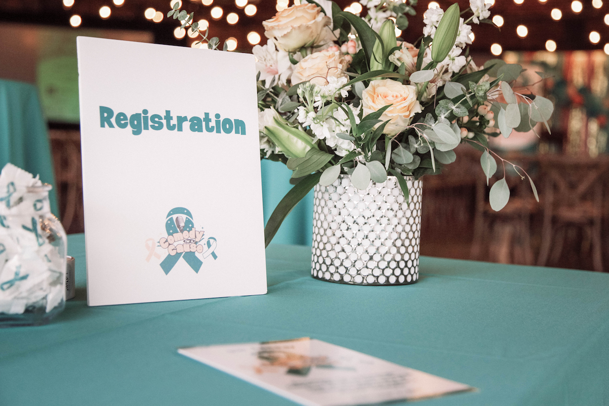 An event registration table with a teal tablecloth representing gynecologic cancer awareness