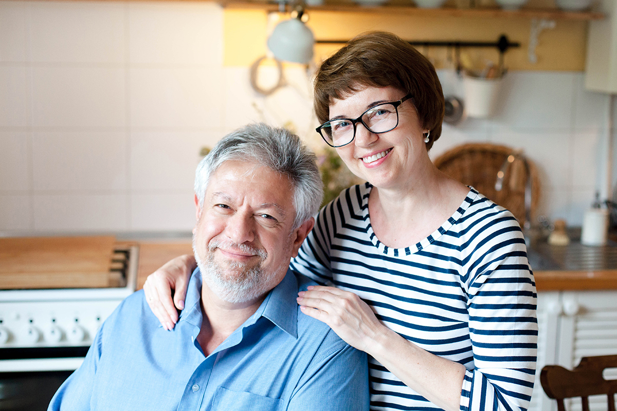 Middle-aged couple standing in their kitchen