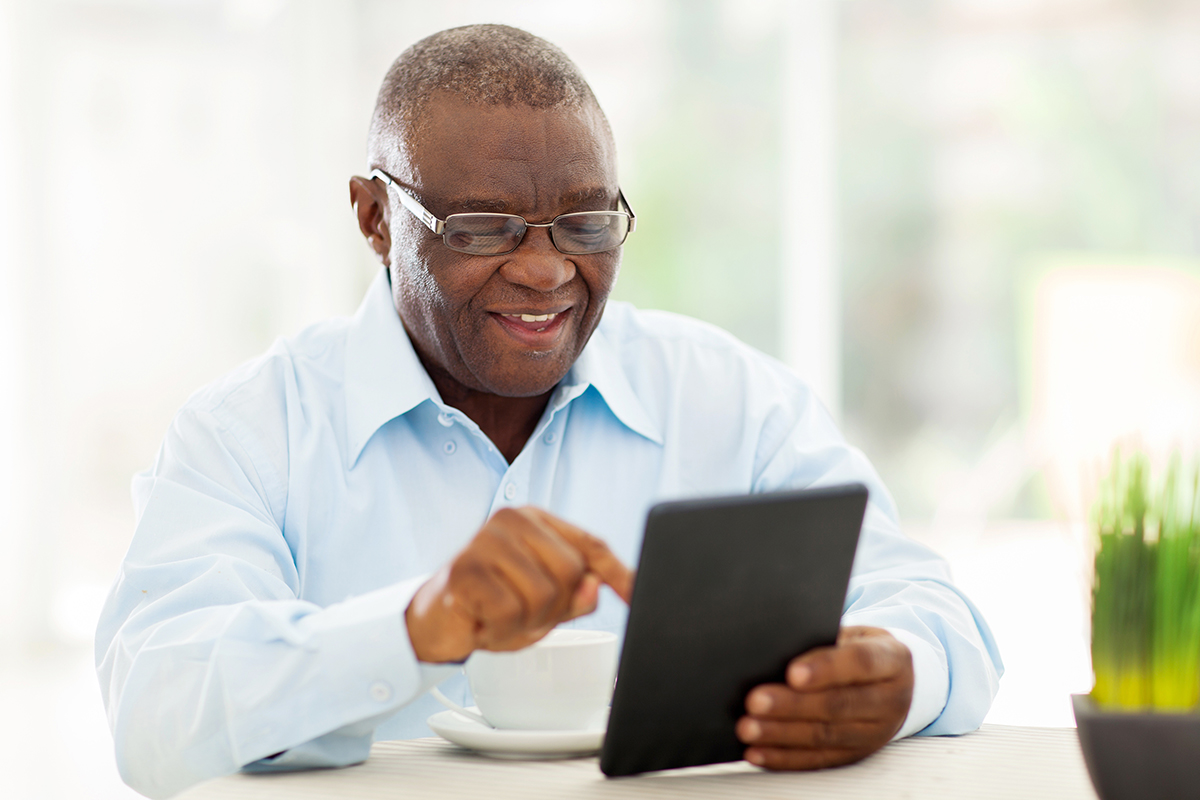 A senior Black man uses a tablet at his dining room table