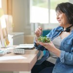 A woman eats a salad while attending an online meeting